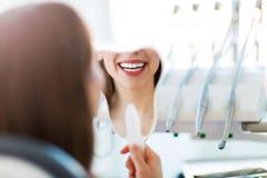 Frau, welche die Zähne überprüft an den Zahnärzten hat lizenzfreies stockbild