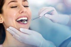Frau, welche die Zähne überprüft an den Zahnärzten hat lizenzfreies stockfoto