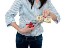 Frau, welche die zehn-Dollar-Banknote mit Scheren kürzt Stockbilder