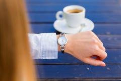 Frau, welche die Zeit auf ihrer Uhr überprüft Stockfotografie