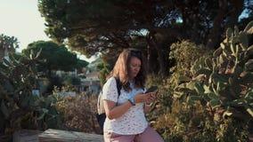 Frau, welche die Zelle im Freien im Sommer verwendet stock video footage