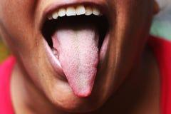Frau, welche die Zunge zeigt Stockfotos