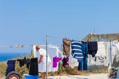 Frau, welche heraus die Kleidung hängt, um im Dorf von Oia auf Santorini-Insel zu trocknen lizenzfreie stockfotos