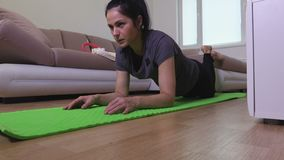 Frau, welche zu Hause die Plankenübung tut stock video footage