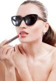 Frau wendet einen roten Lippenstift auf Lippen an. Stockfotografie