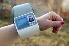 Frau wendet Sorgfalt für Gesundheit mit Herdschlagmonitor und Blutdruck an Stockfotografie
