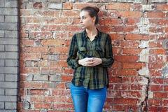 Frau, wenn Wegwerfkaffeetasse auf der Hintergrundbacksteinmauer gestanden wird Lizenzfreie Stockbilder