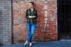 Frau, wenn Wegwerfkaffeetasse auf der Hintergrundbacksteinmauer gestanden wird Lizenzfreies Stockbild