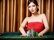 Frau wettet Stapel der Chips, die Roulette spielen Lizenzfreies Stockbild