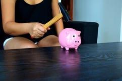 Frau wird ein Sparschwein mit einem Hammer brechen stockbilder