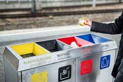 Frau wirft Papierabfall im Abfall, der Abfall sortiert Stockbild