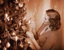 Frau zündet Kerzen auf Weihnachtsbaum. Lizenzfreie Stockfotos