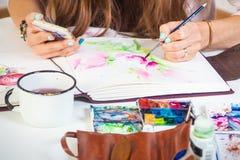 Frau zeichnet Blume lizenzfreie stockfotos