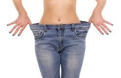 Frau zeigt, dass sie Gewicht verloren hat Große Jeans lizenzfreies stockbild