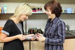 Frau zeigt dem Abnehmer Proben für Manikürenagel Stockbild
