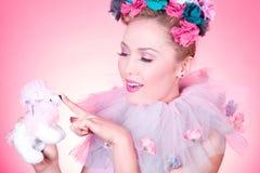 Frau zeigt eine Spielzeugpudelwekzeugspritze Lizenzfreie Stockbilder