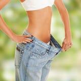 Frau zeigt Gewichtsverlust, indem sie alte Jeans trägt Stockfotografie