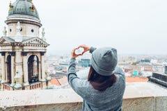 Frau zeigt Herz mit den Händen mit schöner Ansicht der alten europäischen Stadt auf Hintergrund Stockbild