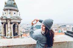 Frau zeigt Herz mit den Händen mit schöner Ansicht der alten europäischen Stadt auf Hintergrund Stockfotografie
