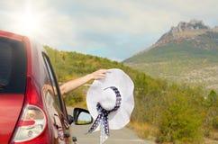 Frau zeigt Sonnenhut vom Auto Lizenzfreie Stockbilder