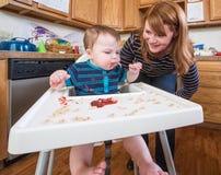 Frau zieht Baby in der Küche ein Stockbild