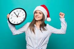 Frau zu der Zeit gesorgt 10 Minuten vor neuem Jahr auf grünem Hintergrund Stockfoto