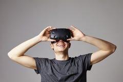 Frau zu Hause, die den Kopfhörer der virtuellen Realität spielt Spiel trägt Stockbild