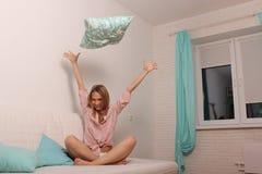 Frau zu Hause im Bett, das Spaß hat und ein Kissen wirft Lizenzfreies Stockbild