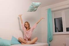 Frau zu Hause im Bett, das Spaß hat und ein Kissen wirft Stockbilder