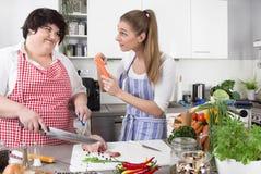 Frau zwei in der Küche - ein dünn, ein Fett - gesunde Ernährung - lizenzfreie stockfotografie