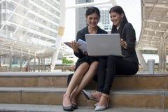 Frau zwei, die das glückliche Arbeiten an Computer lacht lizenzfreies stockbild