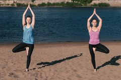 Frau zwei, die das Yoga steht auf dem Strand durch den Fluss in der Stadt ausdehnt Schöne Stadtansicht Balancenhaltung Lizenzfreie Stockfotos