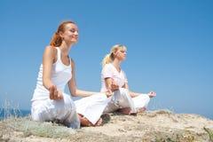 Frau zwei, die in den Bergen meditiert Stockbild