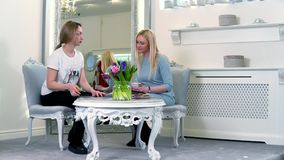 Frau zwei, die nahe dem großen Spiegel in der weißen Luxusboutique sitzt stock video