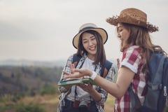 Frau zwei, die Richtung auf Standortkarte beim Reisen sucht stockbild