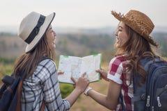 Frau zwei, die Richtung auf Standortkarte beim Reisen sucht stockbilder