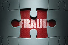 Fraud concept. Missing piece from a jigsaw puzzle revealing the word fraud stock photo