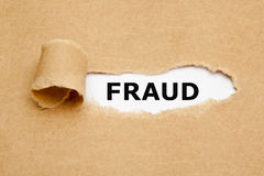 Fraud Torn Paper Concept. The word Fraud appearing behind torn brown paper stock photo