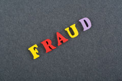 FRAUD word on black board background composed from colorful abc alphabet block wooden letters, copy space for ad text Stock Photos