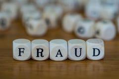 Fraude escrita com cubos de madeira fotos de stock royalty free