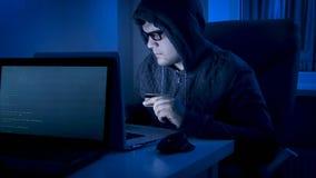 Fraude masculina do cyber que rouba o dinheiro do cartão de crédito bancário usando o portátil Fotografia de Stock
