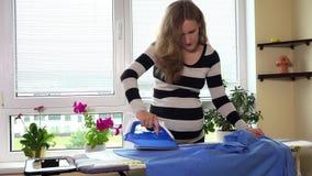 Fraueisenehemann-Mannhemd der schwangeren Frau auf Bügelbrett mit Dampf stock video