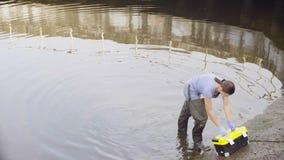 Frauenökologe, der pH des Wassers im Stadtfluß misst stock footage
