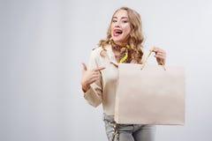 Frauenüberraschung, die Produkt zeigt Schönes Mädchen mit gelocktem Haar p Stockbild