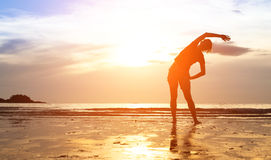 Frauenübung auf dem Strand bei Sonnenuntergang Stockbilder
