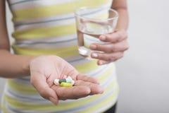 Frauen übergeben das Halten des Glases Wassers einnehmen Medizin Lizenzfreie Stockfotografie