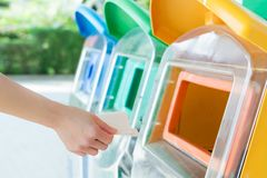 Frauen übergeben den Abfall zum Behälter/zum Abfall wegwerfen und sortieren Abfall/Abfall vor Tropfen zum Behälter Stockbild