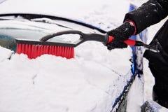 Frauen übergeben im schwarzen Handschuh entfernt Schnee von der Autowindschutzscheibe am Wintertag Lizenzfreie Stockfotografie