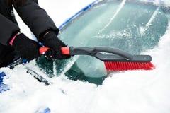 Frauen übergeben im schwarzen Handschuh entfernt Schnee von der Autowindschutzscheibe am Wintertag Stockfotografie