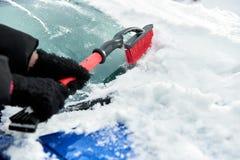 Frauen übergeben im schwarzen Handschuh entfernt Schnee von der Autowindschutzscheibe am Wintertag Lizenzfreies Stockfoto